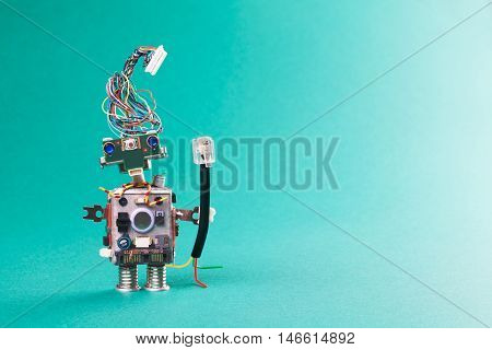Retro robot with network device. Connecting communication concept, stylish computer character blue eyed head, electrical wire hairstyle. Copy space, green background