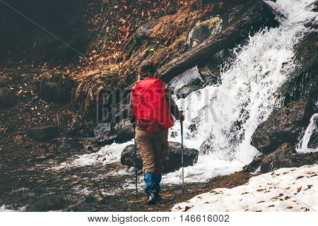 Woman traveler with red backpack hiking Lifestyle adventure vacations concept outdoor waterfall on background rainy moody weather