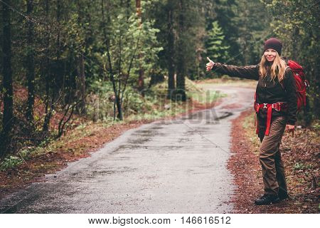 Young Woman with red backpack hitchhiking alone on the road Travel Lifestyle concept