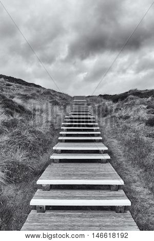 Wooden footpath through dunes at the North sea beach in Germany.