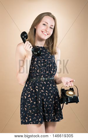Pretty young woman holding vintage telephone