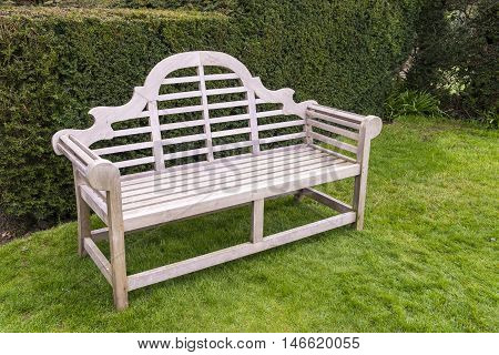 Wooden artisan bench on a grassy lawn.