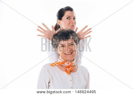 Playful young daughter is holding hands above senior mother as antler - isolated on white