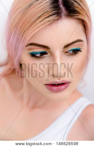 Seductive woman with pink hair and piercing looking at camera