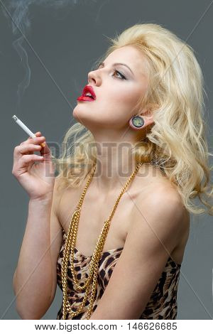 Portrait of young beautiful blond  woman with red lips  in the studio in a beautiful dress smoking a cigarette