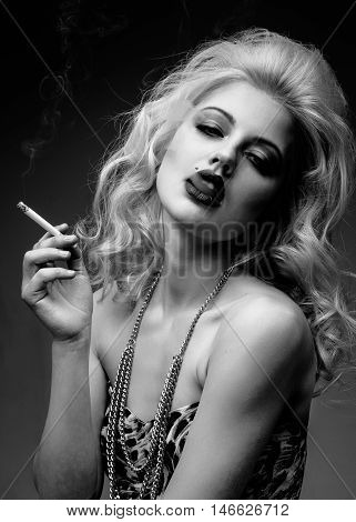 Portrait of young beautiful blond  woman with red lips  in the studio smoking a cigarette black and white
