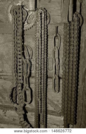 Old rusty chain hanging on the wall. Tool for bicycle. Black and white