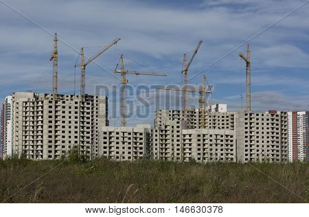Construction of apartment buildings on blue sky background in front of the houses the grass on the Gulf of Finland Residential complex