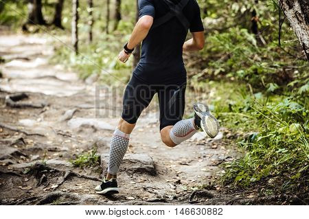 dynamic athlete running marathon in woods. legs in compression socks