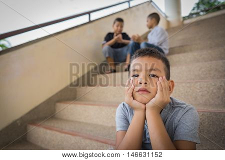 Young Asian boy sitting alone, having been bullied by other children