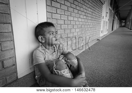 scared and alone, young Asian child who is at high risk of being bullied and abused, selective focus