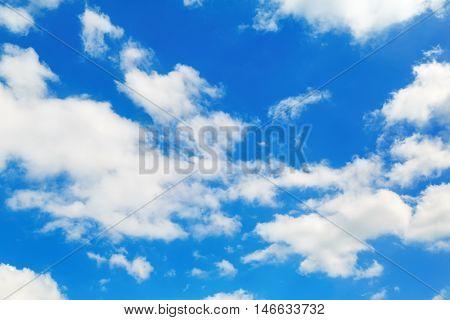 Sky and clouds. White fluffy cumuli clouds in the blue sky.