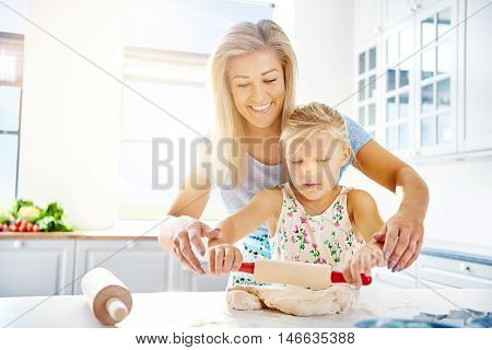 Cute little girl learning to roll out dough as she helps her mother in the kitchen with the baking high key with copy space