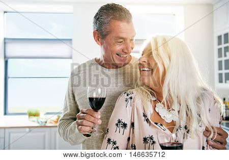 Happy relaxed retired couple deeply in love sharing a glass of red wine in the kitchen smiling into each others eyes high key with copy space