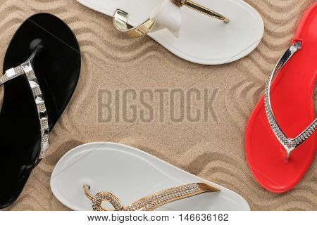 Frame beach flip flops encrusted with rhinestones standing on the sand with space for your text