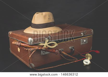 Travel and adventure concept. Vintage brown suitcase with fedora hat, bullwhip, compass and ankh key of life on dark background.