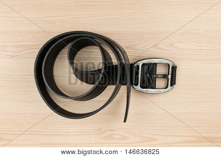Black leather belt with buckle lying on a wooden surface with space for your text