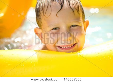Close-up portrait of a boy in swimming pool, outdoor shoot