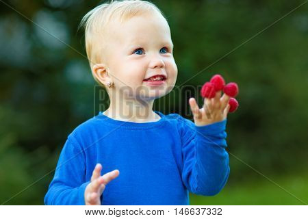 Young girl is holding raspberries on her fingers, outdoor shoot