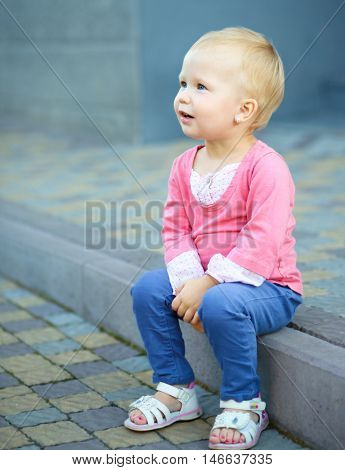 Portrait of a child sitting on border, outdoor shoot