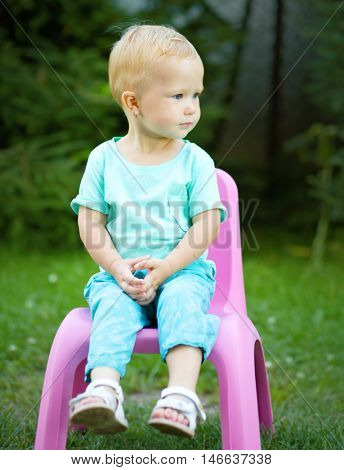 Portrait of a child sitting on plastic chair, outdoor shoot