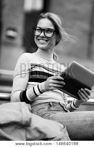 Student looks sitting near underpass with tablet in hands, black and white photo