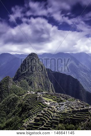 Vertical picture of the lost Inca city of Machu Picchu. Machu Picchu archaelogical ruins in the clouds on the blue sky. Photo from above.