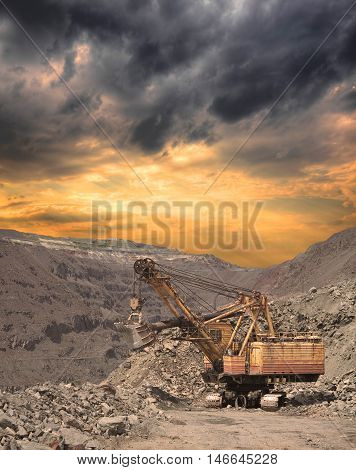 Large excavator on the iron ore opencast on stormy sunset