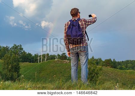 A tourist with a backpack landscape photographs on your phone. A guy with a beard in a plaid shirt with a backpack meets sunset in nature. A lone traveler. Rainy clouds and a rainbow. Unity with nature.