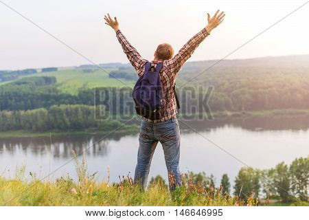A man with a backpack on a mountain. The guy in a checkered shirt put his hands up to the sky. Freedom and unity with nature. Sun going down. Tourist outdoors enjoying the scenery.