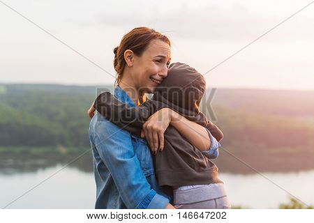 Mother hugging her son and crying. Unity with nature emotional stress. The concept of family values feelings and emotions.