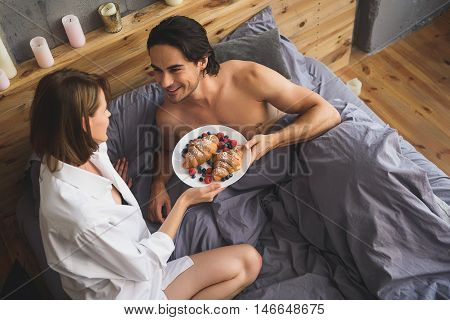 couple holding plate with croissants while lying in a bed