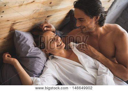 Happy young couple lying in their bed at home and looking at each other