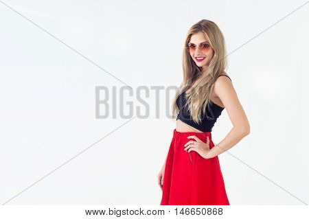 Young blond model presenting new fashionable summer look, wearing circle sunglasses, red skirt and black sleeveless top close-up front view portrait