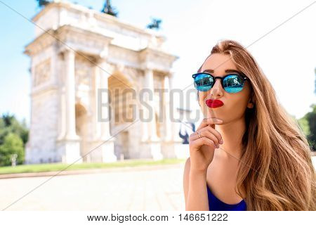 Young woman dreaming about vacations on the famous triumphal arch backround