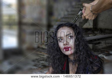women hand sleeve pointing gun on vampire women head. A woman at gunpoint