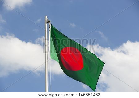 National flag of Bangladesh on a flagpole in front of blue sky
