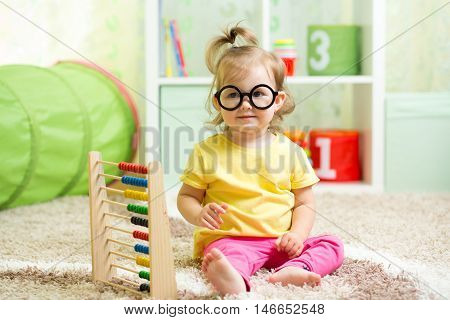 kid girl with eyeglasses playing with abacus toy
