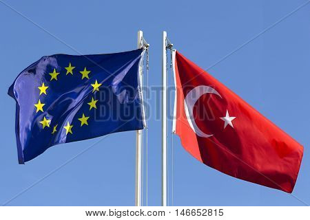 European Union flag and flag of Turkey on flagpole in front of blue sky