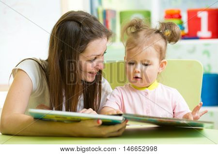 Happy mother and daughter reading a book together in nursery