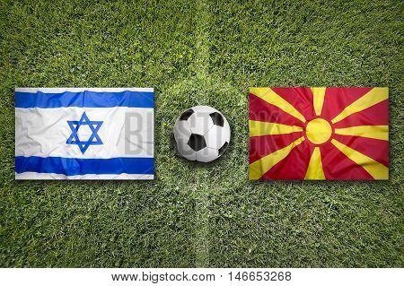 Israel Vs. Macedonia Flags On Soccer Field, 3D Illustration