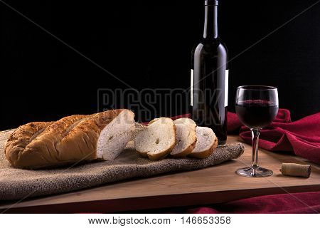 Slices from a loaf of french bread and an wine glass and wine bottle.