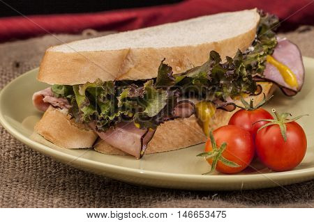 Delicious ham sandwich with lettuce and mustard and cherry tomatoes on the side.