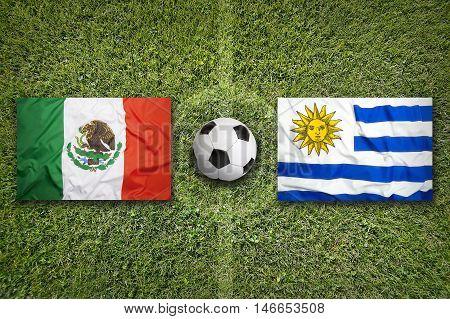 Mexico Vs. Uruguay Flags On Soccer Field, 3D Illustration