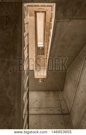 Looking up on cement modern stairway stairs with symmetrical lines