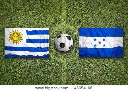 Uruguay Vs. Honduras Flags On Soccer Field, 3D Illustration