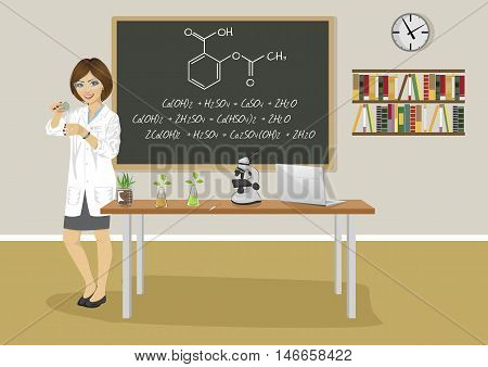 school female teacher giving a lecture in chemistry class next to blackboard