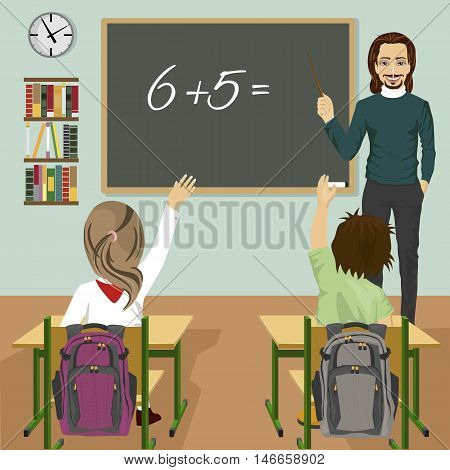male teacher writing mathematic task on a green chalkboard in classroom and children raising hands up