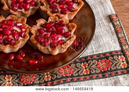 Four tartletes with custard and pomegranate in brown plate on linen tablecloth with ethnic pattern.