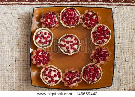 Tartletes with custard and pomegranate in big brown plate on linen tablecloth. Aerial view.